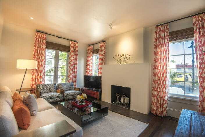 A comfortable living room with a mid century flare, fireplace and just the right splash of orange and blue coloring in the drapes and chairs in a historic Burns ct. bungalow in downtown Sarasota renovated by custom home builder Nautilus Homes