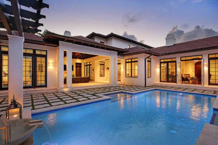 View of a pool at a custom home with a British West Indies Architecture style in the spice bay neighborhood on siesta key built by Nautilus Homes
