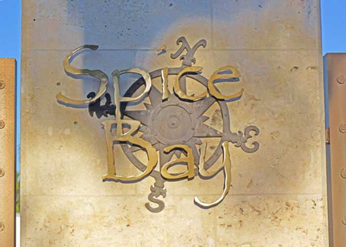The spice bay logo cut from steel and mounted to a coral clad pillar