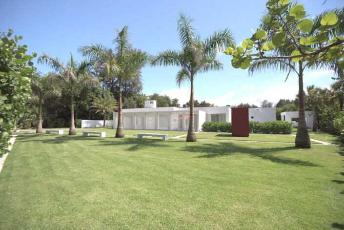 White mid century modern home with circular cement screen, lush zoysia sod mixed with concrete elements, large royal palms and a red reading pod renovations by luxury home builder Nautilus Homes